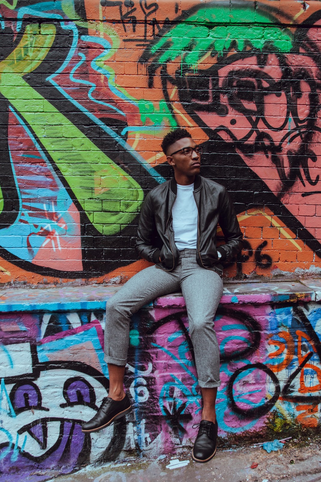 A young man casually sits on a ledge with graffiti behind him. He is wearing a leather bomber jacket, white shirt, grey pants, and black oxford shoes.